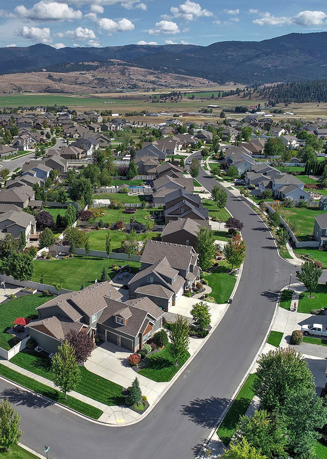 Aerial view of Spokane houses, with mountains in the background.