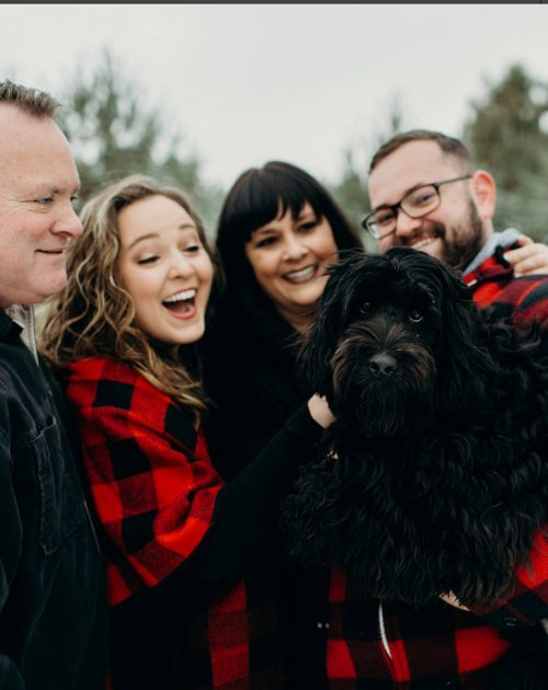 Winter photo of Amy with her family and dog.